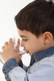 Child drinking water. Handsome child drinking water in whie background Stock Photo