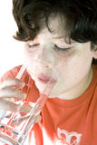 Child drinking water. Boy drinking water, white background royalty free stock image