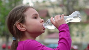 Child drinking water from bottle outdoor. Young girl with water bottle in hand