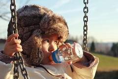Child drinking water from feeder Stock Images