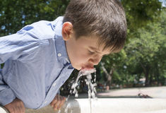 Child drinking water from a fountain Stock Image