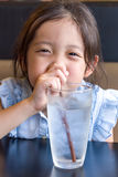 Child Drinking Water from Glass. Using straw stock images