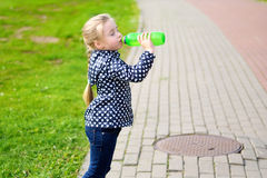 Child drinking water in nature. On autumn Stock Photo