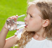Child drinking water outdoors Stock Images