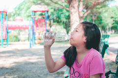 Child drinking water in park. Royalty Free Stock Photography