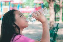 Child drinking water in park. Royalty Free Stock Photos