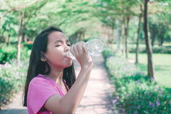 Child drinking water in park. Royalty Free Stock Photo