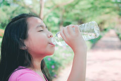 Child drinking water in park. Little girl drinking water in park Royalty Free Stock Photo