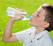 Child drinking water at summer Royalty Free Stock Image