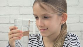 Child Drinking Water, Thirsty Kid Studying Glass of Fresh Water, Girl in Kitchen royalty free stock images