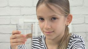 Child Drinking Water, Thirsty Kid Studying Glass of Fresh Water, Girl in Kitchen stock photos