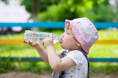 Child drinks from  bottle in park. 2 years child drinks from plastic bottle in park Stock Images