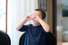 A child drinks a glass of water stock photography