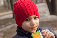 The child drinks juice in the Playground. emotional close-up portrait. stock photos