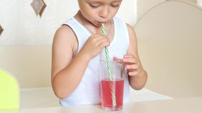 A child drinks juice through a straw from a glass beaker stock footage