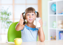 Child drinks milk and showing thumb up. Child girl drinks milk and showing thumb up Stock Photography