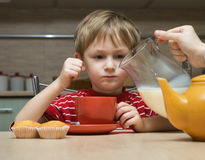 Child drinks tea with milk Stock Photography