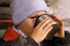 Child drinks from thermos cup Stock Images