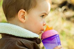 Child drinks water from a baby bottle Royalty Free Stock Photography