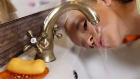 Child drinks water from the bathroom faucet. Closeup, sliding camera stock video