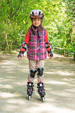 Child drives Roller Skates. In a park Royalty Free Stock Photography
