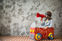 Child driving in a car made of cardboard box. Child driving a car made of cardboard box. Kid having fun at home. Travel and vacation concept Royalty Free Stock Photos