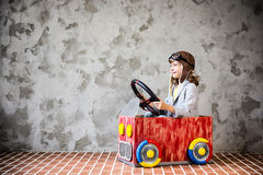 Child driving in a car made of cardboard box Stock Images