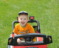 Child driving toy car. A boy laughing and driving a jeep through the grass Stock Photo