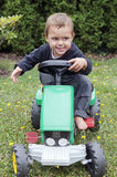 Child driving toy tractor Stock Image