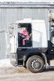 Child driving a truck. A child plays in the truck driver. child turns the wheel of a large truck. Little girl driving a big truck Stock Photo