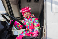 Child driving a truck. A child plays in the truck driver. child turns the wheel of a large truck. Little girl driving a big truck Stock Photography