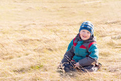 Child on dry grass (field) Royalty Free Stock Photography