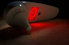 Child Ear Thermometer High Red. A 3D render of an infant ear infrared thermometer illuminated with a red light and the word high signifying danger on an isolated Royalty Free Stock Images