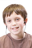 Child with earbuds. Isolated child with earbuds listening to music or audio books stock photography