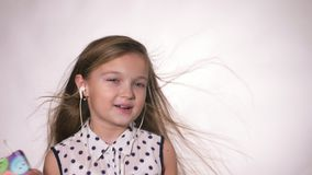 Child with earflaps dancing at studio background. The girl listens to music on the smartphone. The kid has loose long hair. Shooted on a gray white background stock video footage