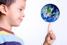 Child and earth. Child taking the earth on his finger with a gesture of happiness royalty free stock photography