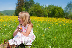 Child on Easter egg hunt. Little girl on a beautiful sunlit meadow in spring on an Easter egg hunt having just found a nest Stock Photos