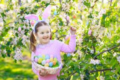 Child with bunny ears on garden Easter egg hunt Stock Photo