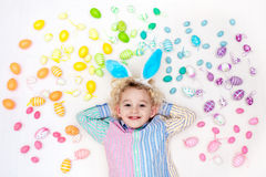 Child on Easter egg hunt. Pastel rainbow eggs. Royalty Free Stock Photography