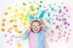 Child on Easter egg hunt. Pastel rainbow eggs. Funny little boy with bunny ears having fun on Easter egg hunt. Child playing with colorful Easter eggs. Kids stock photo