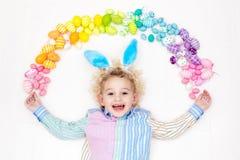 Child on Easter egg hunt. Pastel rainbow eggs. Stock Image