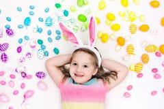 Child on Easter egg hunt. Pastel rainbow eggs. Stock Images