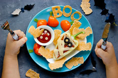 Child eat colorful vegetarian dinner or lunch in Halloween style Royalty Free Stock Photos