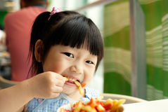 The child eat fries. Concentrate on the child to eat Fries Royalty Free Stock Image