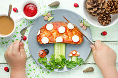 Child eat funny brunch from toast with tomato sauce, cheese and. Cucumber shaped mushroom on vegetables greens forest glade. Fun with food composition top view Stock Photo