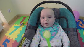 Child eat porridge sitting in car seat. Hand feed baby spoon. 4K stock video