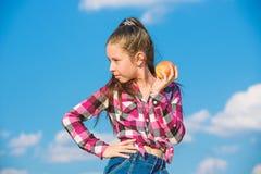 Child eat ripe apple fall harvest. Fruit vitamin nutrition for kids. Apple fruit diet. Kid hold ripe apple sunny day. Kid girl with long hair eat apple blue stock photos