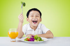 Child eat salad and drink orange juice Royalty Free Stock Photos