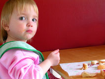 Child Eating. Little girl eating with small fork and bib Royalty Free Stock Photo