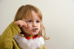 Child eating. Young cute girl eating with teaspoon Stock Photography